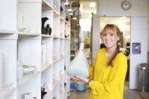 Mulher segurando vaso de cerâmica na oficina — Fotografia de Stock