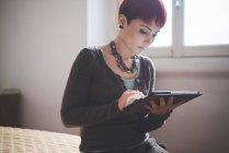 Jeune femme à la maison à l'aide de tablette numérique — Photo de stock