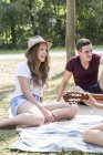 Grupo de jóvenes sentados sobre la manta de picnic, mujer joven tocando guitarra - foto de stock