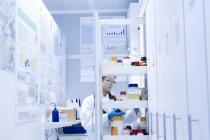 Female scientist selecting specimen jar from shelves in laboratory — Stock Photo