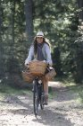 Mature woman cycling with foraging baskets on forest path — Stock Photo