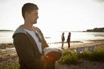 Молодий чоловік тримає ковдру на Борнмут Біч, Дорсет, Великобританія — стокове фото