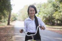 Девочка с велосипедом на проселочной дороге в Камбодже — стоковое фото