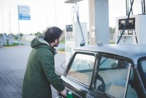 Man using fuel pump for vintage car in gas filling station — Stock Photo
