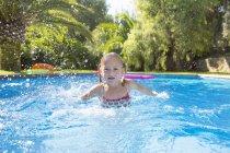Girl swimming in garden swimming pool — Stock Photo