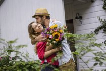 Young couple with bunch of flowers hugging in garden — Stock Photo