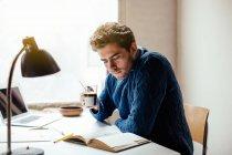 Jeune homme lisant livre avec café — Photo de stock