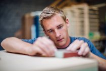 Surface vue de niveau de charpentier mâle à l'aide de papier de verre dans l'atelier — Photo de stock