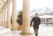 Young man carrying xmas gift in Covent Garden, London, UK — Stock Photo