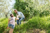 Low angle view of young man helping young woman up hill — Stock Photo