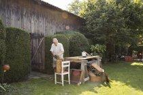 Ältere Mann, der hölzerne Kiste im Garten — Stockfoto
