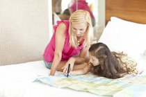 Mother and daughter lying on bed, looking at map — Stock Photo