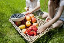 Brother and sister taking fruits from basket — Stock Photo