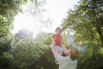 Padre sosteniendo a su hijo pequeño en el soleado parque - foto de stock