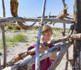 Boy placing driftwood to construct shelter, Caleri Beach, Veneto, Italy — Stock Photo