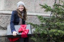 Portrait de femme d'âge mûr avec cadeau de Noël à côté de l'arbre de Noël — Photo de stock