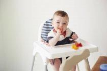 Bébé garçon manger des légumes dans la chaise bébé — Photo de stock