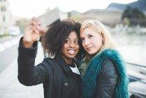 Two young women posing for selfie at lakeside — Stock Photo