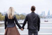 Vista posteriore di romantica giovane coppia di fronte al fiume Tamigi , — Foto stock