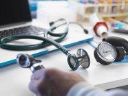 Arzt holt Auriskop mit Stethoskop und Blutdruckmessgerät vom Schreibtisch — Stockfoto