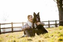 Портрет середині дорослої жінки сидять зі своєю собакою в галузі — стокове фото