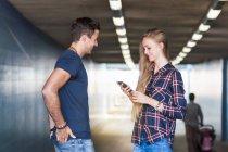 Casal jovem, lendo o texto de smartphone em viaduto — Fotografia de Stock