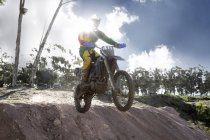 Young male motocross racer jumping mid air down mud hill — Stock Photo