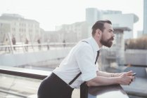 Stylish businessman with smartphone looking out from office balcony — Stock Photo