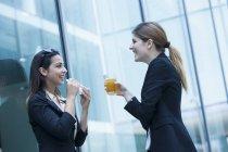 Деловые женщины обедают с бутербродами и пьют по офисному зданию — стоковое фото