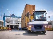 Caminhão que descarrega recipientes da balsa ao porto — Fotografia de Stock