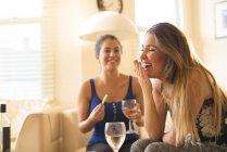 Две молодые женщины с девочками ночуют, пьют и смеются — стоковое фото