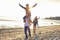 Homens dando passeio de piggyback para mulheres na praia — Fotografia de Stock