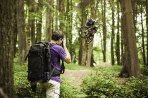 Jeune photographe masculin photographiant un VTT en forêt — Photo de stock