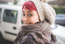 Portrait of young woman looking over shoulder, smiling, wearing winter clothes — Stock Photo