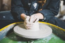 Cropped view of young woman sitting at pottery wheel making clay pot — Stock Photo