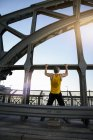 Un homme fait des tractions sur un pont, Munich, Bavière, Allemagne — Photo de stock