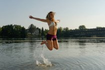 Partially dressed mid adult woman, jumping in lake — Stock Photo