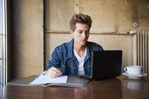 Молодий учень, сидячи в кафе таблиці за допомогою ноутбука і робити нотатки — стокове фото