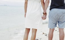 Куповані заднього виду молода пара, тримаючись за руки на пляжі, Kradan, Таїланд — стокове фото