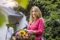 Portrait of young woman with basket of flowers in garden — Stock Photo