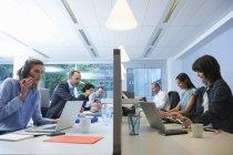 Бизнесмены сидят по разные стороны экрана и работают — стоковое фото