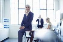 Portrait of young businesswoman sitting on office desk — Stock Photo