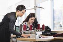 Дві швачки дивлячись на швейну машину в майстерні — стокове фото