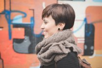 Young woman by graffiti wall — Stock Photo