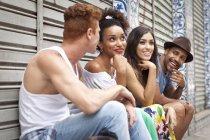 Gruppo di amici seduti insieme, ridendo e sorridendo — Foto stock