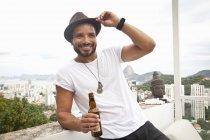 Uomo che beve sulla terrazza, Sugarloaf Mountain sullo sfondo, Rio, Brasile — Foto stock