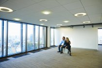 Mature business couple looking from empty office window at Brussels cityscape, Belgium — Stock Photo