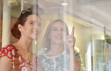 Two young women looking and pointing at shop window — Stock Photo