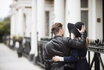Rear view of romantic young couple strolling on street, London, England, UK — Stock Photo
