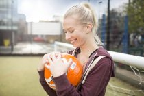 Young woman holding football, smiling — Stock Photo